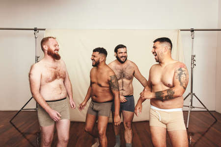 Laughter in the studio. Group of self-confident young men laughing cheerfully while wearing underwear in a modern studio. Four shirtless young men embracing their natural bodies. Фото со стока