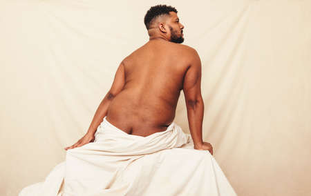 Naked man sitting in a studio. Rearview of a nude man looking away while sitting on a studio curtain. Body positive and self-confident young man embracing his natural body.