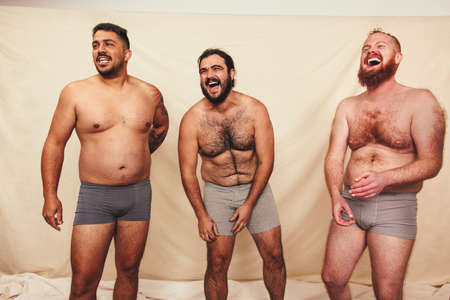 Three shirtless men laughing cheerfully in a studio. Body positive men wearing underwear and standing together against a studio background. Self-confident men embracing their natural bodies. Фото со стока