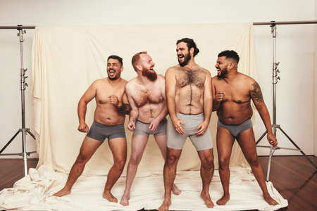 Being natural is fun. Four body positive young men laughing cheerfully while standing together in underwear. Self-confident young men embracing their natural bodies in a studio. Фото со стока