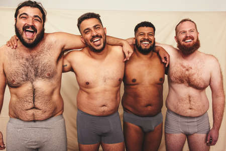 Studio shot of shirtless men embracing each other. Four happy men smiling at the camera while wearing underwear. Body positive and self-confident men embracing their natural bodies.