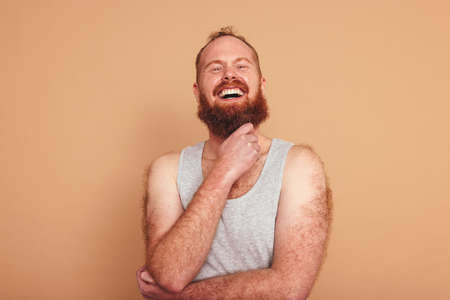 Cheerful man smiling at the camera in a studio. Body positive young man standing against a studio background. Self-assured young man feeling comfortable in his natural body. Фото со стока