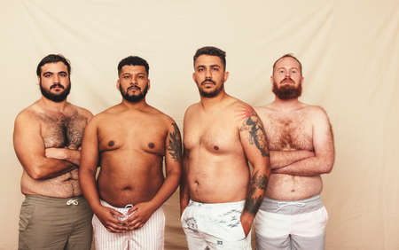 Men standing together in a studio without shirts. Four body positive young men looking at the camera confidently. Group of self-assured men embracing their natural bodies.