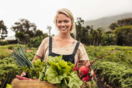 Vegetable farmer smiling cheerfully after harvest. Happy young woman holding a box full of freshly picked produce in her vegetable garden. Successful female farmer standing on an organic farm.