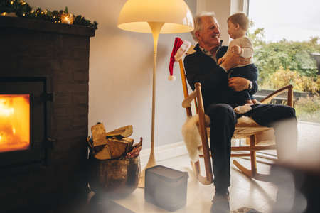 Elderly man with a small boy sitting on chair at home by fireplace. Senior man with grandson on christmas eve.