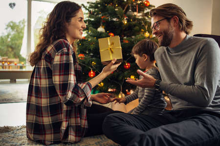 Couple sitting by Christmas tree with their son exchanging gifts at home. Beautiful small family celebrating Christmas at home.