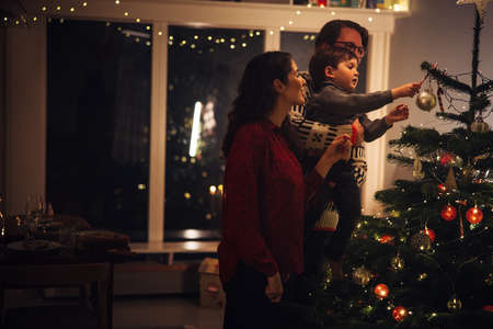 Small family decorating Christmas tree together at home. Parents with child decorating home for Christmas celebrations. Фото со стока