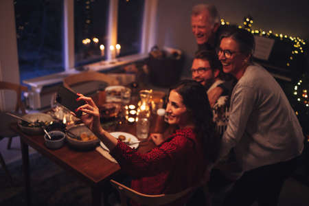 European family talking selfie on mobile phone during Christmas dinner at home. Focus on mobile phone and female hand taking selfies. Фото со стока