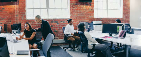 Businesspeople working in a creative modern workplace. Group of young businesspeople interacting with each other while sitting at their desks. Colleagues teaming up and sharing ideas.