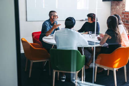 Creative businesspeople having a discussion in a meeting room. Experienced mature businessman leading a meeting in a modern office. Group of creative businesspeople working as a team.