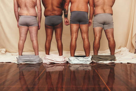 Anonymous men standing in a studio with their shorts dropped down. Rearview of a group of body positive men standing together in underwear. Self-confident men flexing their natural bodies.