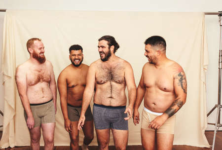 Body positivity in the studio. Group of self-confident young men laughing cheerfully while wearing underwear in a modern studio. Four shirtless young men embracing their natural bodies.