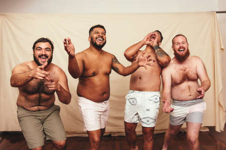Cheering in the studio. Four body positive men celebrating while standing together against a studio background. Group of shirtless young men embracing their natural bodies.