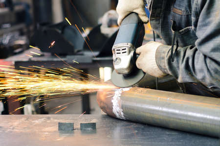 erector: Front view of the grinding tool to smooth the weld metal. Working with the tool. Stock Photo