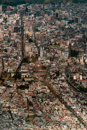 quito: High angle view of Quito streets. Old houses in the foreground with modern ones in background.
