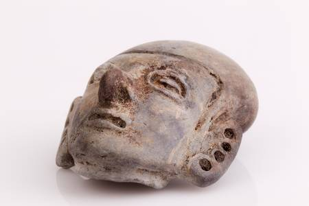 indigenous culture: antique amulet from Valdivia culture representing an abstract beeing on white background. Part of La Tolita region, north of Ecuador in Esmeralda province. Stock Photo