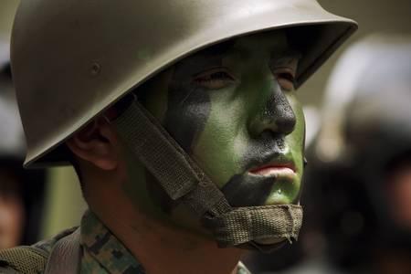 BANOS DE AGUA SANTA,ECUADOR- 11 DECEMBER 2010: Ecuadorian soldier with having his face painted in camouflage pattern IN BANOS DE AGUA SANTA,ECUADOR- 11 DECEMBER 2010