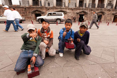 latin child: Quito,Ecuador - 14 September 2010 : Young boys that use to shine shoes  for living are happy to pose for everyone who gives them 1$, Quito,Ecuador - 14 September 2010 Editorial