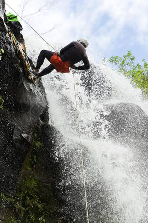 Man desceding a huge waterfall in Ecuadorian rain forest