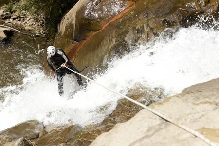 adult man desceding an ecuadorian waterfall in a corect position photo