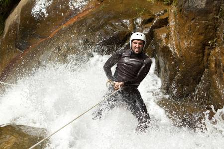 torrent: adult man desceding an ecuadorian waterfall in a corect position Stock Photo