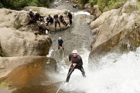 adult man desceding an ecuadorian waterfall in a corect position Stock Photo
