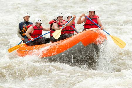 Un grupo de hombres y mujeres, con una guía, rafting en el río Patate, Ecuador