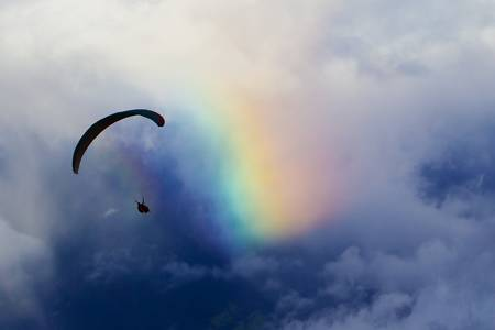 Paraglider against cloudy sky and natural rainbow. Could suggest the human attraction for colors. photo