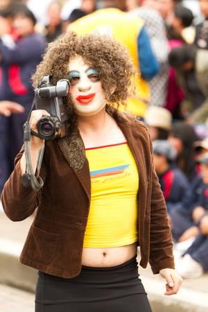 Pillaro,Ecuador - January 6, 2012: Man desguised as gringo tourist woman with a camera during the Diablada of Pillaro celebration in  Ecuador.