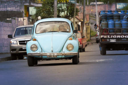 widely: Banos de Agua Santa,Ecuador - August 11, 2012 : Old fashioned car driving on the street of Banos de Agus Santa. The Volkswagen Type 1, widely known as the Volkswagen Beetle, was an economy car produced by the German auto maker Volkswagen .Tinted for more  Editorial