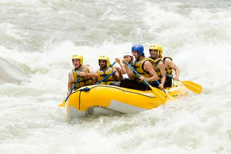 rapid: a group of men and women, with a guide, white water rafting on the Pastaza river, Ecuador