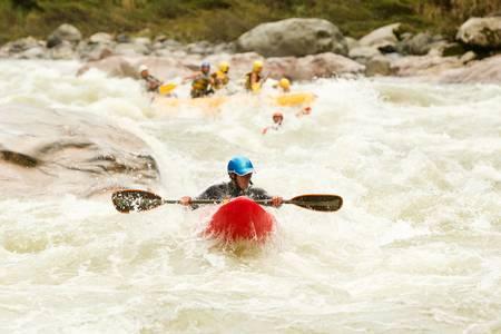large rafting boat chasing a kayak on Pastaza river, ecuador