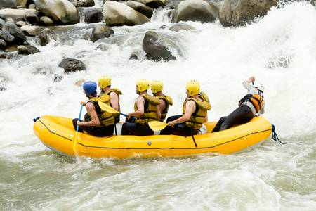 rowing boat: a group of men and women, with a guide, white water rafting on the Pastaza river, Ecuador