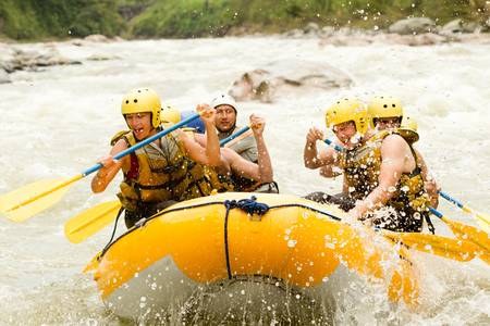 rowing: a group of men and women, with a guide, white water rafting on the Pastaza river, Ecuador