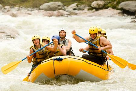 adventure sports: a group of men and women, with a guide, white water rafting on the Pastaza river, Ecuador
