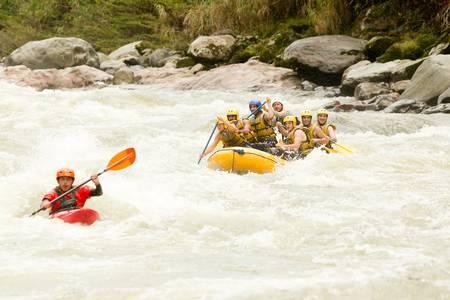 whitewater: large rafting boat chasing a kayak on Pastaza river, ecuador