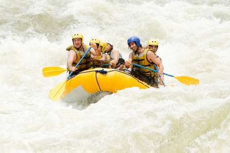 to soak: a group of men and women, with a guide, white water rafting on the Pastaza river, Ecuador