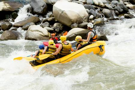 persevere: a group of men and women, with a guide, white water rafting on the Pastaza river, Ecuador