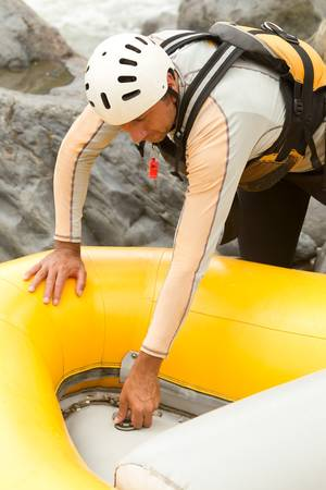 raft: rafting boat maintenance, the pilot preparing the boat for the next adventure.
