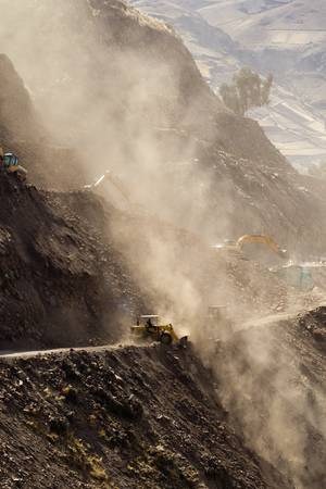 mining machinery: road building in Ecuadorian Andes at high altitude, vertical.