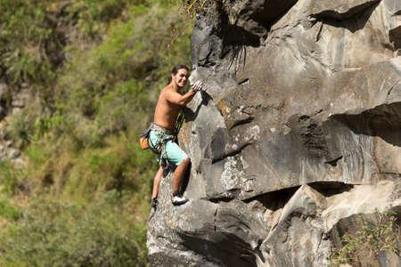 powe: rock climber climbing up a cliff Stock Photo