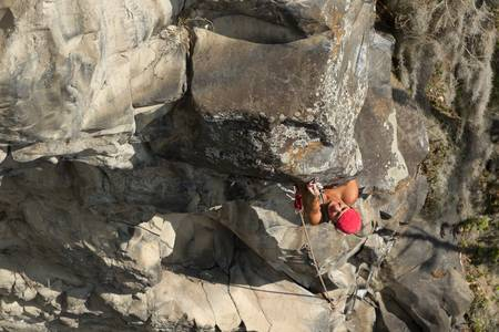powe: rock climber climbing up a cliff Stock Photo