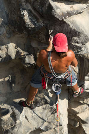 rock climb: rock climber climbing up a cliff Stock Photo