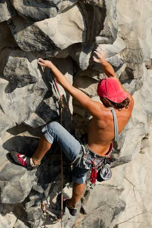 climbing sport: rock climber climbing up a cliff Stock Photo