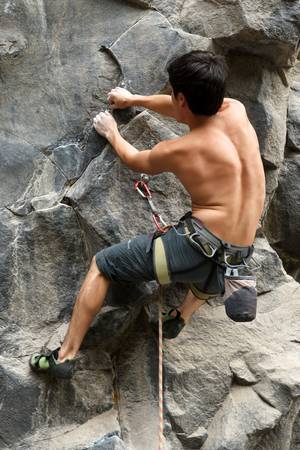 Rock climber holding from a very tinny hall in the rock Stock Photo - 16250788