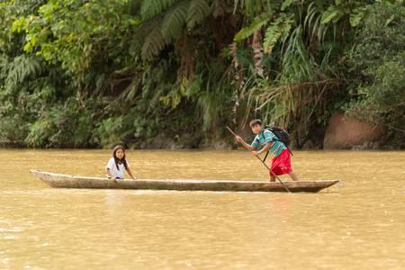 amazonia: Puni Bocana,Ecuador - November 16,2012: Two local kids from Puni Bocana village returns from school by raft. Ecuadorian Amazonia Editorial