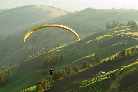 Paraglider over farmed land in beautiful sunset light ,seen from air photo