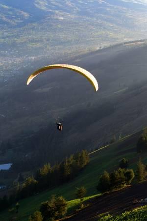parapente: Ala flexible sobre las tierras cultivadas en luz hermosa puesta de sol, visto desde el aire