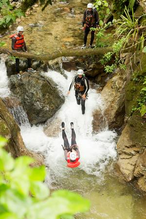 BACKFLIP: canyoning team performing a backflip into a small waterfall