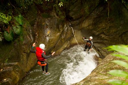 well equipped man jumping into a natural pool during a canyoning expedition photo